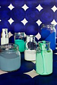 Various paints in glass jars on length of blue patterned wallpaper