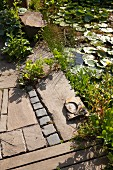 Wooden deck and paved terrace next to lily pond