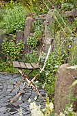 Rusty garden chair with wooden seat on grey paved terrace in garden