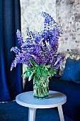 Blue and purple flowering lupins in preserving jar on pastel blue side table