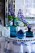 Lupins in blue glass vases on console table with lace trim and gathered fabric below antique mirror