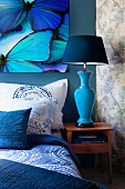 Bed with blankets, pillows and scatter cushions in shades of blue below picture of butterflies; blue bedside lamp on small cabinet