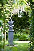 Modern sculpture on plinth in landscaped garden