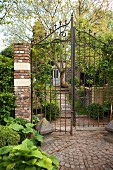 Open, wrought iron garden gate with brick gatepost and view of idyllic cottage surrounded by garden