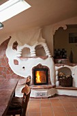 Stove and fireplace surround modelled in organic forms with terracotta tiles in open-plan kitchen-dining room of rustic holiday apartment
