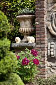 Romantisches Gartenarrangement mit bepflanzter Amphore, Katzenfiguren und blühender Pingstrose