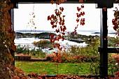 View through climber-covered veranda pillars into autumnal garden on Norwegian skerry coast