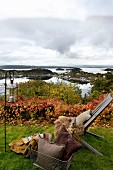 Garden chair with warm fur blankets, cushions and lantern in autumnal garden with view of Norwegian skerry coast