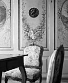 Elegante Stühle vor holzverkleideter Wand mit aufgemalten Blumengirlanden