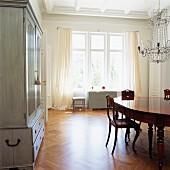 Helles, geräumiges Esszimmer mit antiken Möbeln und prunkvollem Deckenkerzenleuchter