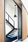 Blick von aussen durch eine schräge Glasschiebetür und vertikale Sichtschutzlamellen auf Leuchtenbündel über puristischer Stahltreppe