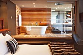 Bedroom with designer, open-plan ensuite bathroom; free-standing, white bathtub against wood-clad wall