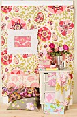 Stack of floral cushions below picture frame on pastel, patterned wall covering next to vintage cabinet draped with bolts of fabric