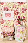 Kissenstapel mit floralen Kissenbezügen vor pastell gemusterter Wandbespannung und Bilderrahmen, daneben Vintagekästchen mit Stoffbahnen drapiert