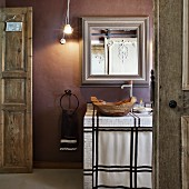 Rustic bathroom with wooden bowl as sink on tiled washstand below mirror on mauve wall
