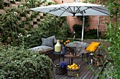 Comfortable seating area on terrace with open parasol surrounded by greenery