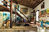 Rustic interior with brick floor and round timber gallery; Brazilian paintings and altar table with figures in shades of blue venerating the sea goddess Lemanja