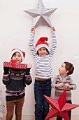 Children holding up Christmas decorations