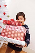 Girl holding Christmas gifts, smiling