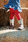 Female toddler with oversized boots
