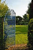 Open, blue iron gate showing view of expansive garden