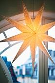Beleuchteter Weihnachtsstern aus Pappe vor einem Rundbogenfenster