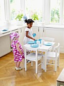 Little girl setting children's table