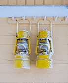 Two snowy lanterns hanging from coat pegs on wooden facade