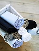 Basket of rolled bed sheets