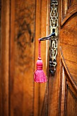 Key with pink tassel in antique wooden door