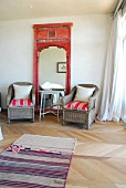 Comfortable corner in bedroom with two wicker armchairs flanking mirror with ornate wooden frame
