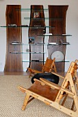 Creative shelving made from slices of tree trunk with glass shelves and wooden armchairs with leather seats and backs in spacious interior