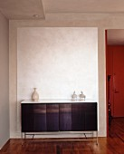 Sideboard with sparse ornaments against white panel on exposed concrete wall