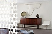 Objets d'art above and on sideboard with dark, exotic wood veneer and white, ornamental partition element in foreground