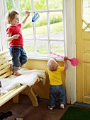 Two toddlers playing with fly swats on veranda