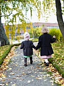 Two children wearing winter coats walking along path holding hands