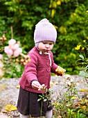 Little girl investigating flowers in garden