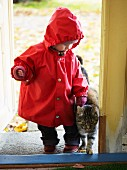 Toddler in raincoat & cat walking into house