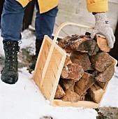 Adult stacking firewood in log basket