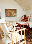 Sofa, wooden chairs & side table in attic living room with sloping ceiling