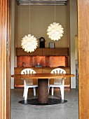 View of kitchen counter with copper-coloured rear wall, round dining table & two modern pendant lamps