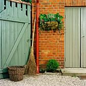 Reisigbesen, Weidenkorb & herbstlich bepflanzter Hängekorb am Haus