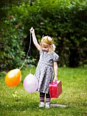 Little girl with crown, balloons & small suitcase in garden
