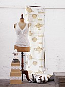 Lace top on old tailors' dummy; curtain with kitchen motifs in background