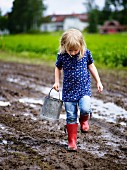 Little girl holding bucket playing in mud