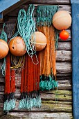 Nets and fishing buoys hanging on weathered wooden wall