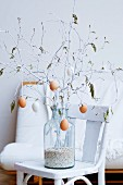 Easter bouquet of white-painted spring branches hung with blown eggs in large glass vase