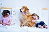 Little girls and dog on white couch