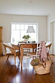 Wooden table, wicker chairs and white-painted cane chairs below pendant lamp