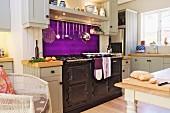 weiße Küche im Landhausstil mit leuchtend violettem Spritzschutz und großem Herd mit Metallfront
